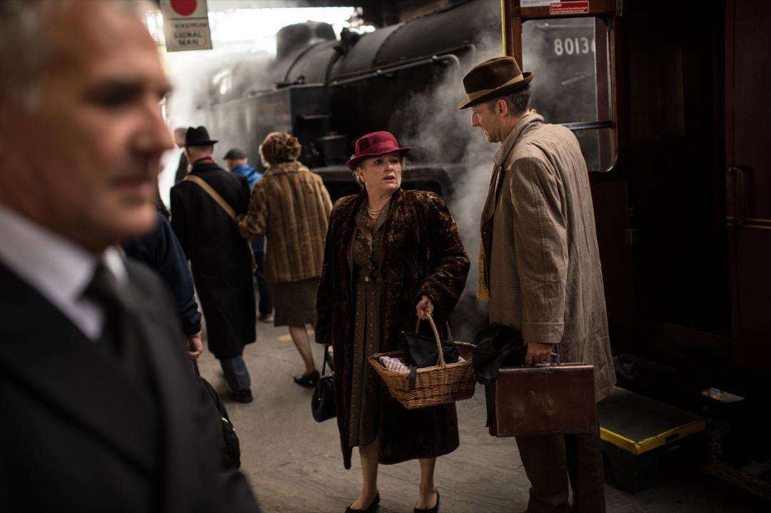 一名婦女與男士在月台上聊天。