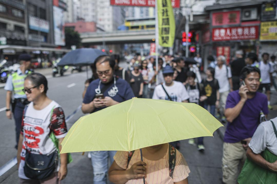 民陣十一遊行,有參加者舉起代表雨傘運動的黃傘參與。