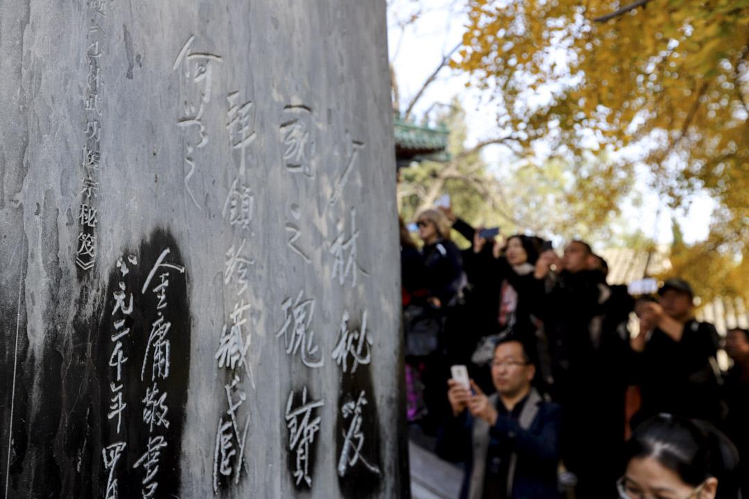 2018年11月2日,河南嵩山少林寺,民眾在少林寺天王殿門前的金庸石碑送上菊花,悼念逝世的金庸。