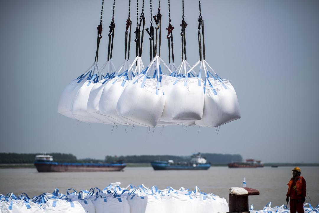 目前有相當多的跡象顯示,中美貿易戰有擴大和常態化的可能。圖為2018年8月7日,工人在中國江蘇張家港的一個港口卸下貨物。