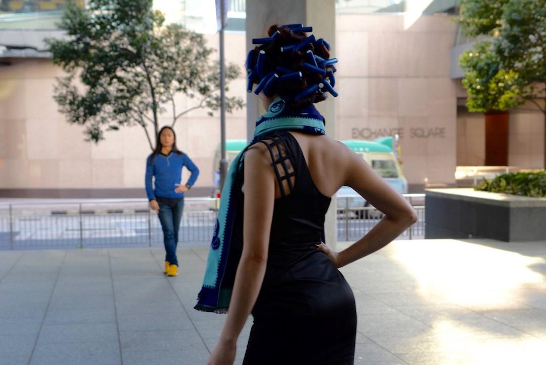 戴著髮捲的菲傭在同樣是菲傭的朋友指導下練習走台步。