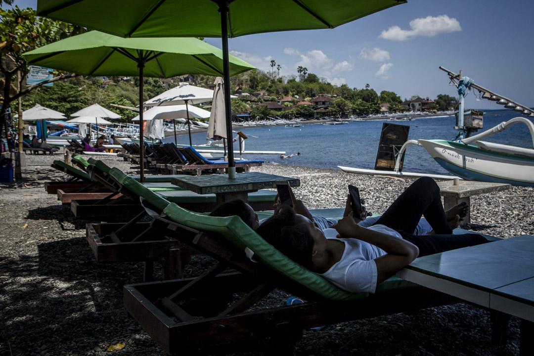 峇里島度假村沙灘上,遊人坐在沙灘椅上看手機。 攝:Ulet Ifansasti/Getty Images