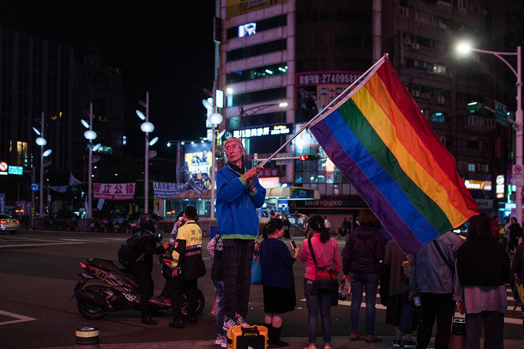 知名同運人士祁家威在公投前於台北西門町高舉彩虹旗。