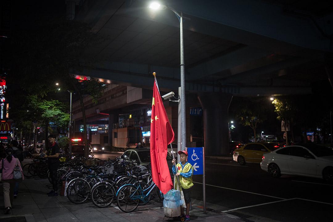 2018年11月21日,鄭建炘的小兒子在捷運站前舉起五星旗。