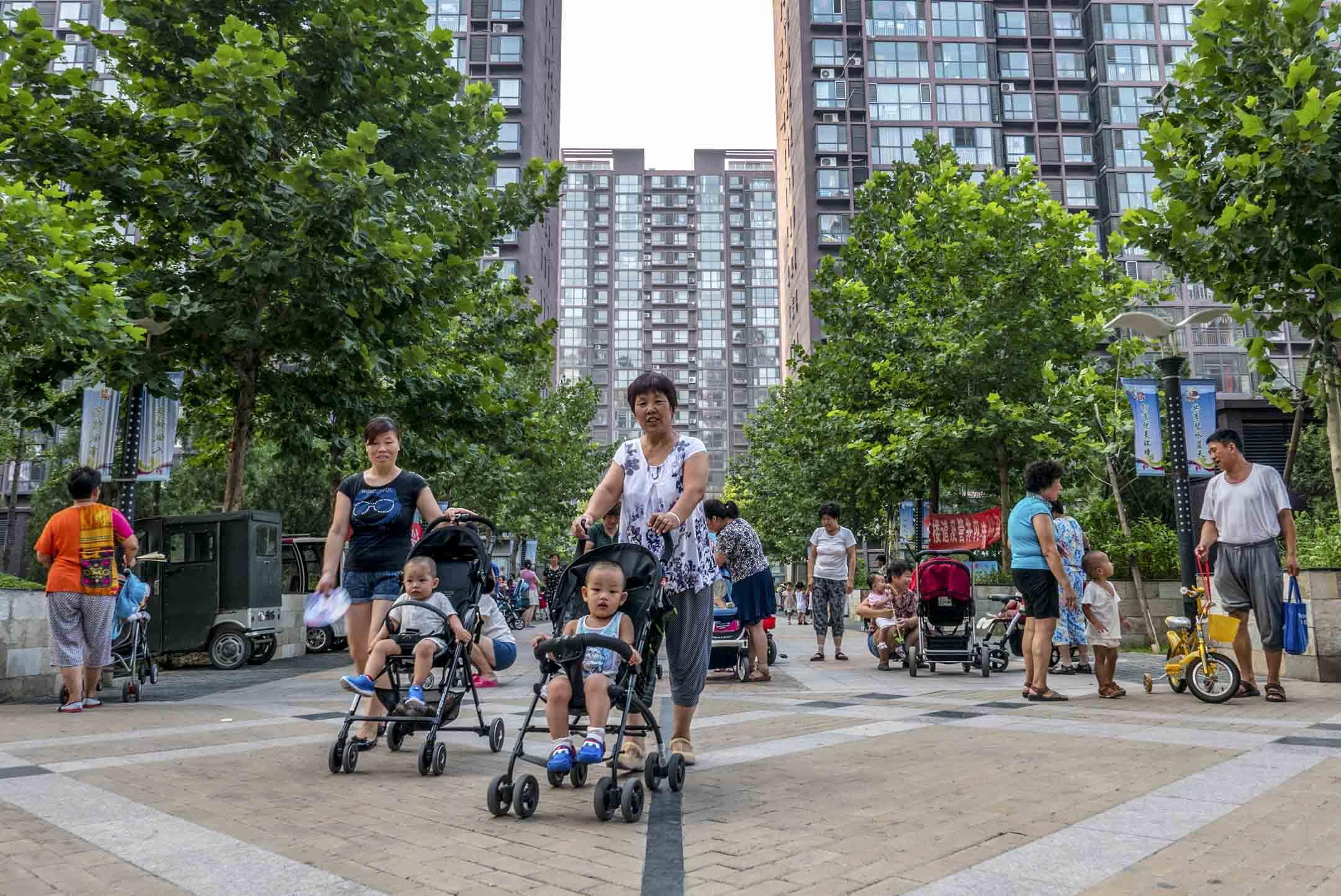 血緣,是祖輩照顧孫輩最正當的理由。祖父母雖有時難以接受先進的育兒理念,同住一個屋檐下也難免有摩擦磕絆,但在李媛眼中,他們才是最無私、最可靠、也最盡心盡力的人選。圖為孩子們跟祖父母在北京一個住宅的社區內玩耍。 攝: Zhang Peng/LightRocket via Getty Images