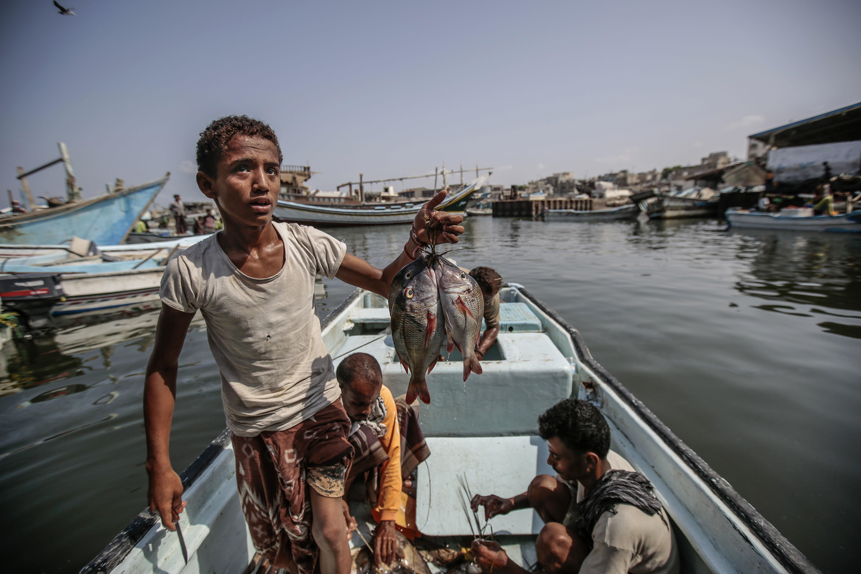 年輕漁民展示一天辛勤後的漁獲。