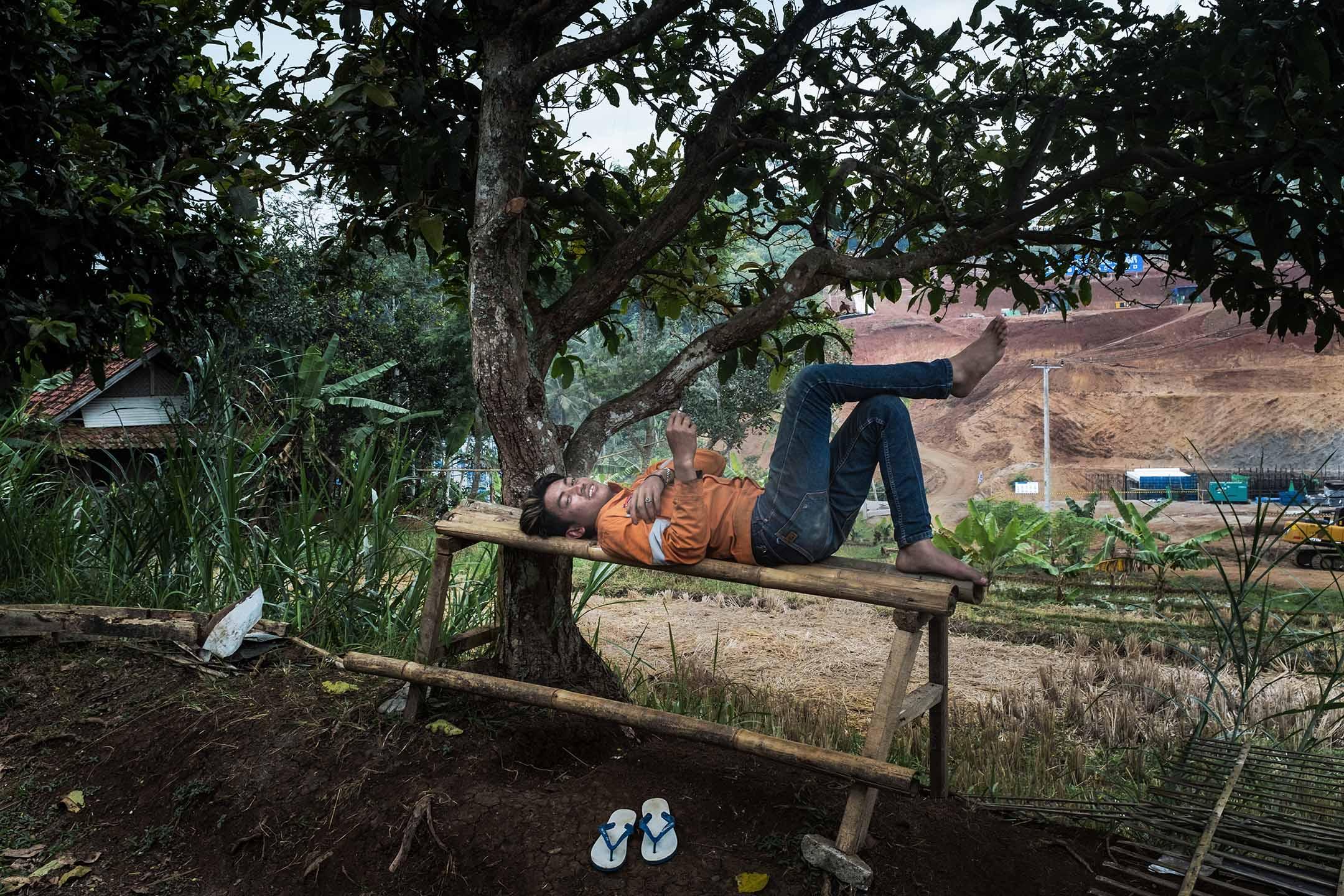 印尼雅萬高鐵碰上徵地問題,進度嚴重落後。圖為一名工人在雅萬高鐵隧道工地前休息。 攝:陳焯煇/端傳媒
