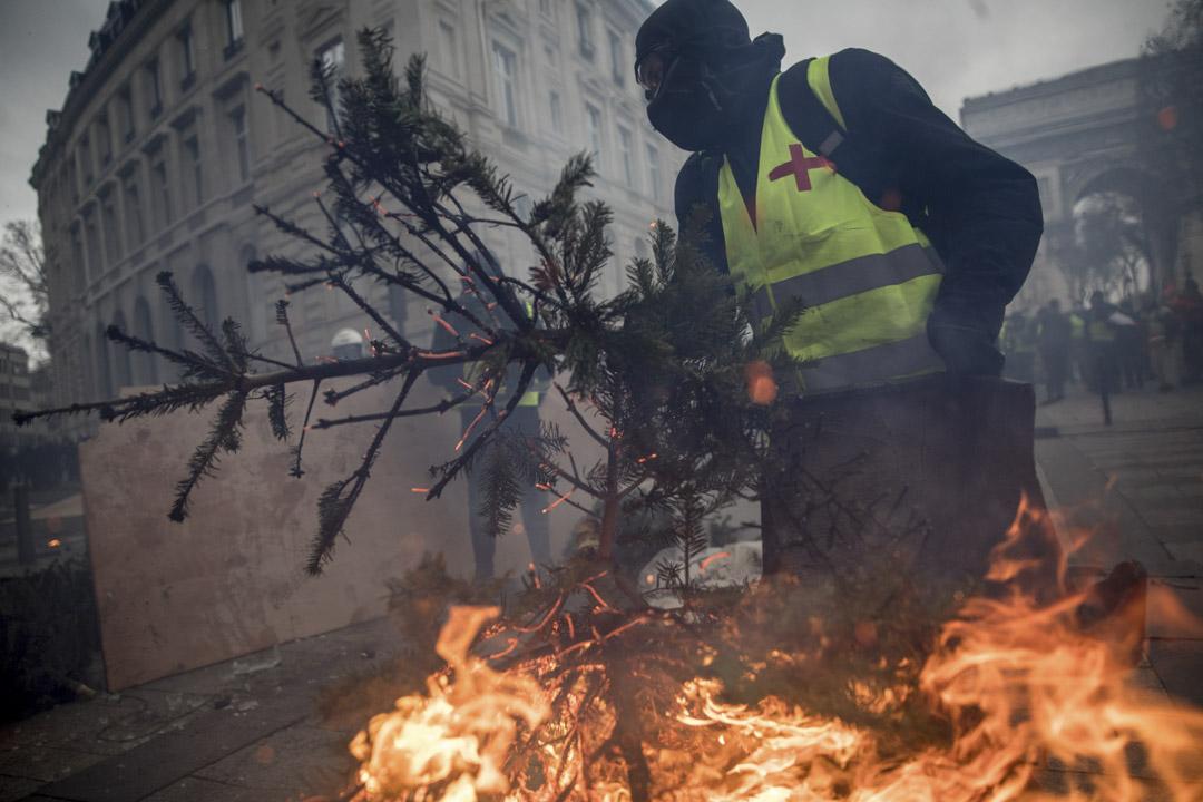 2018年12月8日,一名抗議者將一棵燃燒的聖誕樹帶到街上。