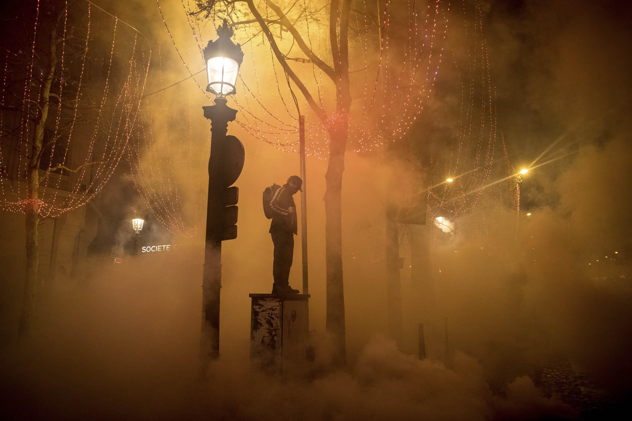 2018年12月8日,巴黎凱旋門附近的香榭麗舍大街上,一名示威者站在催淚氣體之中。