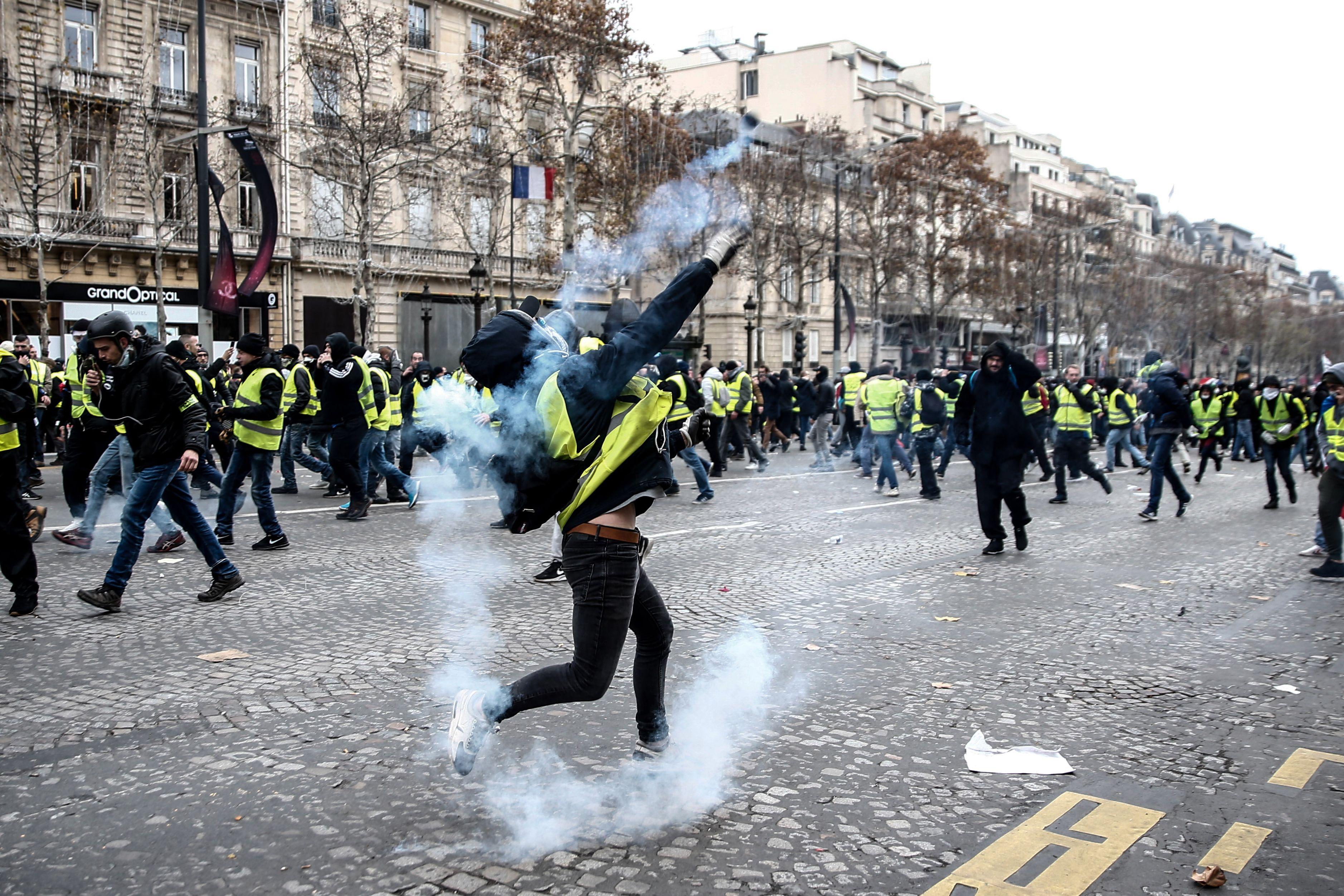 2018年12月8日,示威者在巴黎香榭麗舍大街上與防暴警察衝突,向警察投擲催淚彈。