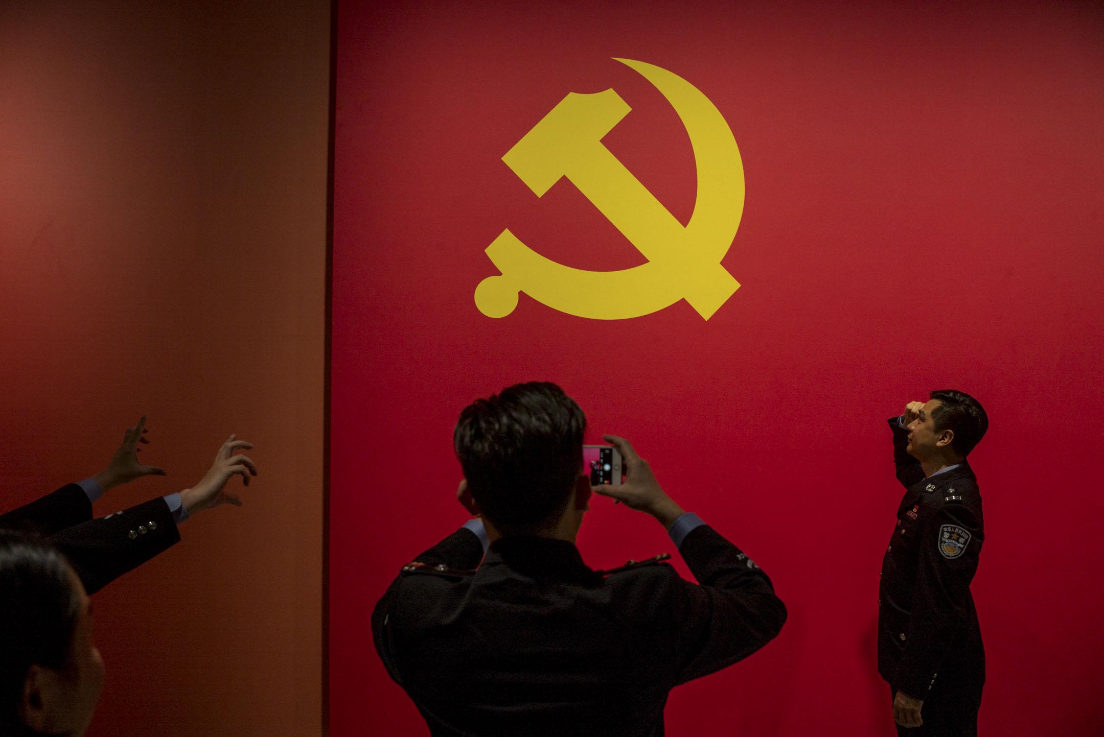 孔杰榮:只要共產黨仍保持其對於權力的壟斷,法治在中國取得實質進展的可能就希望渺茫。圖為2018年11月「大潮起珠江――廣東改革開放40週年展覽」,其中長展品有一幅共產黨黨旗掛在牆上,參觀的警察在旗前拍照。 攝:林振東/端傳媒