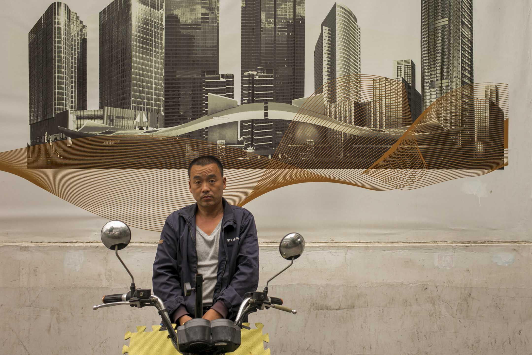 一名富士康工人在以深圳高廈為背景的廣告板前。 攝:林振東/端傳媒