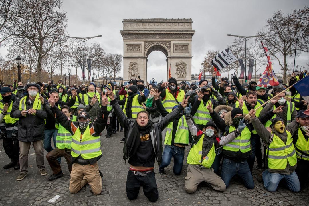 2018年12月8日,法國巴黎,穿上黃馬甲的示威者在凱旋門前跪下,高呼口號。 攝:Chris McGrath/Getty Images