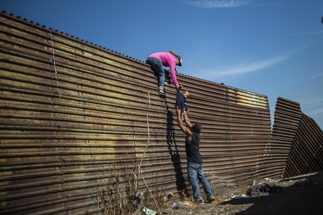 2018年11月25日,墨西哥蒂華納的一段美墨邊境,一批中美洲移民攀上了邊境圍牆上,預備翻越圍牆到美國尋求庇護。 攝:Pedro Pardo/AFP/Getty Images