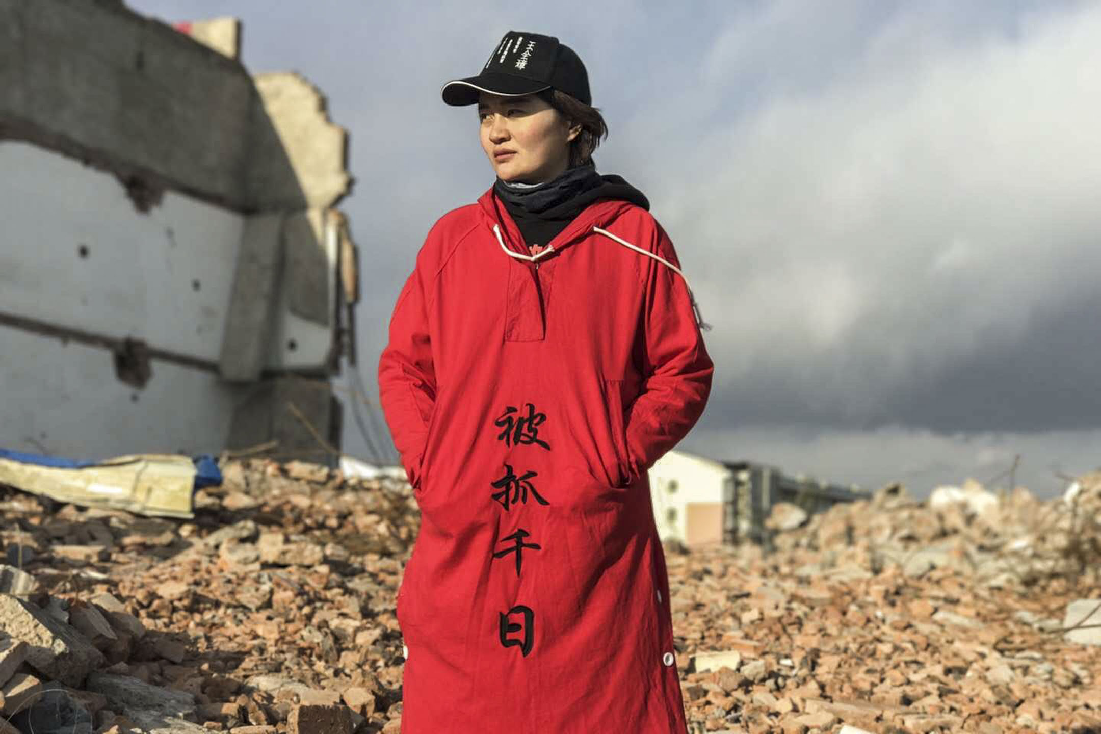 李文足站在剛剛被拆遷、滿目蒼夷的廢墟上,帶着憂傷的笑容,照片上的她,眼睛裏似乎有淚,大紅的衣服上,繡着幾個黑字:「被抓千日」。 圖:受訪者提供