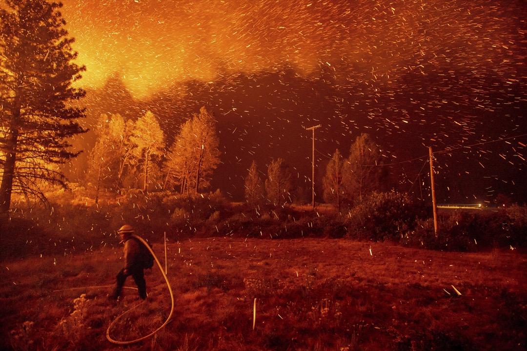 2018年9月6日,美國加州山火持續燃燒,餘燼在一名消防員的頭頂橫飛。