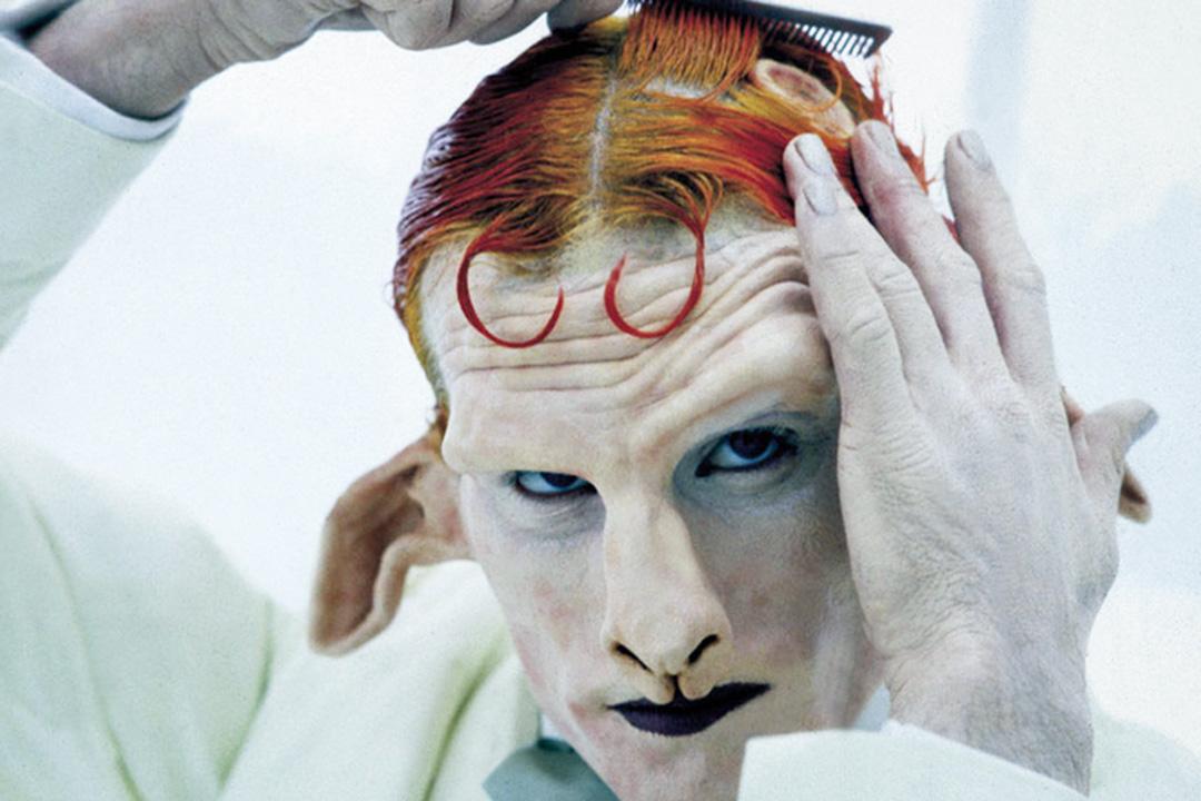 電影一開場,我們便看到巴尼本人扮演的半人半山羊神獸,對鏡梳理一頭烈焰般的金橘色頭髮。圖為電影《懸絲4》 劇照。