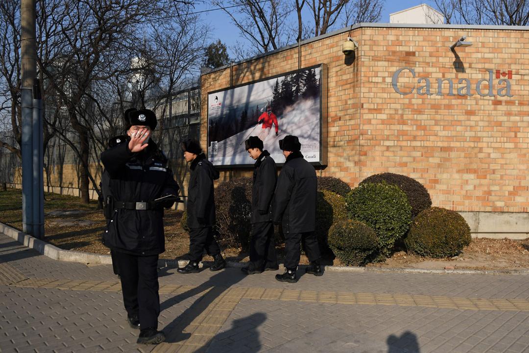 加拿大當局於當地週二(18日)證實再有一名加國公民在中國被捕。圖為2018年12月14日在加拿大駐中國大使館外,一名中國公安準備阻止攝影師拍照。 攝:Greg Baker / AFP / Getty Images