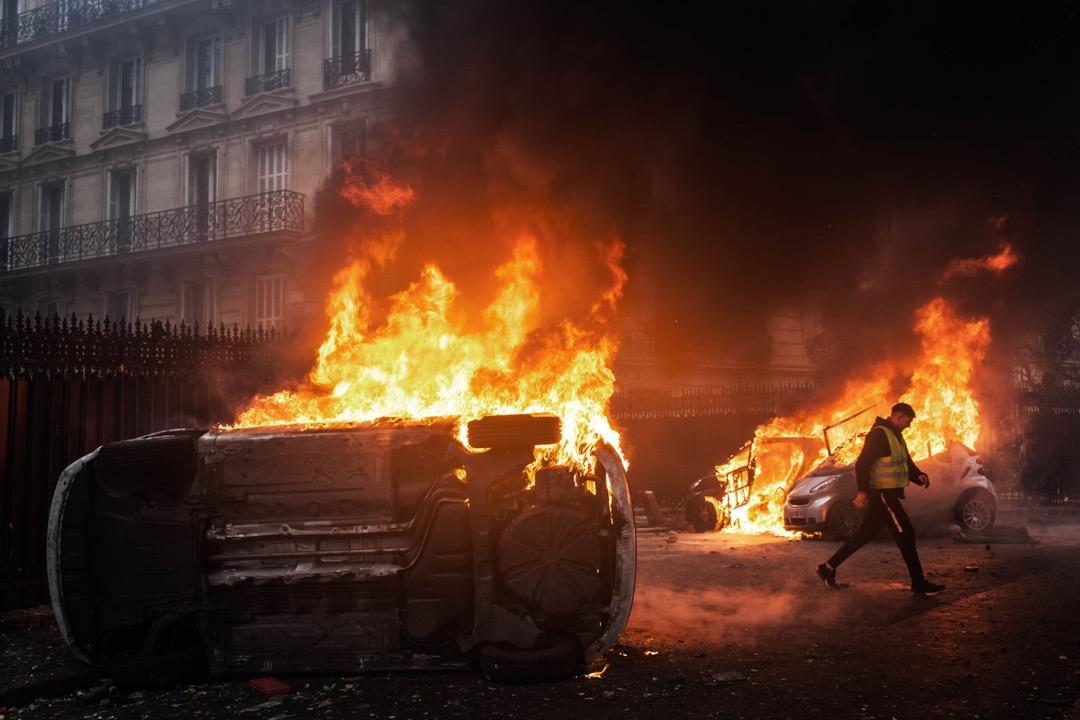 一名示威者走過兩架在示威中被焚毀的車。