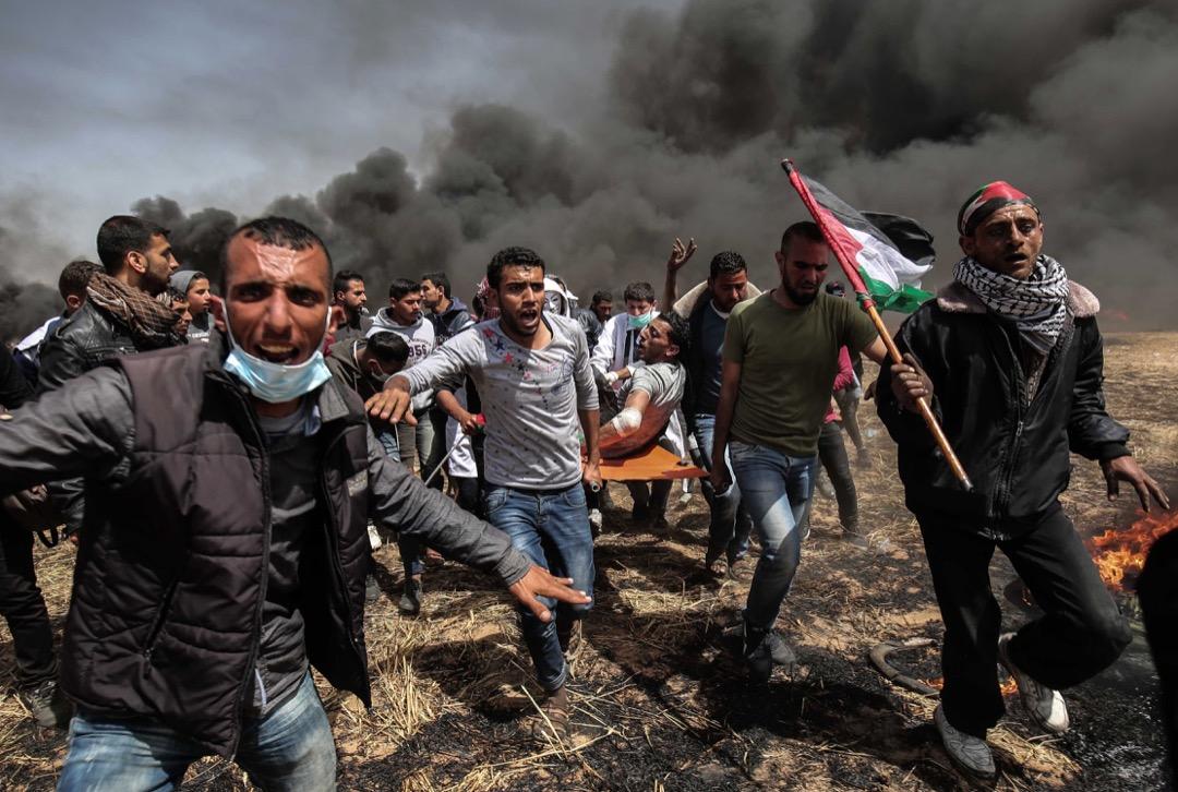 2018年4月6日,巴勒斯坦加沙地帶,數名巴勒斯坦示威者抬著一名在衝突中受傷的示威者到安全地方。