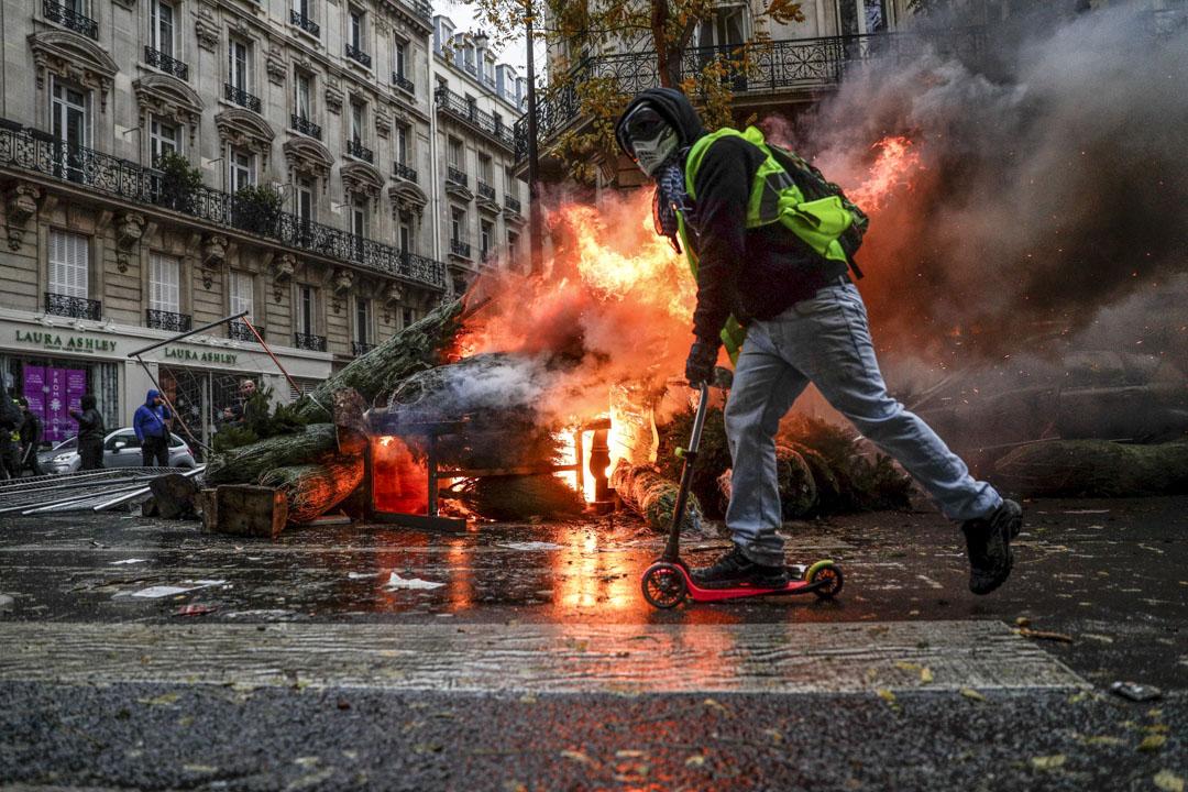 2018年12月1日,一名戴上面罩的示威者在一架被焚毀的車輛前經過。 攝:Geoffroy Van Der Hasselt/AFP/Getty Images