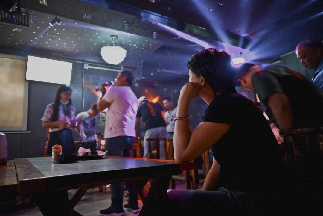 同志酒吧正中一側有個三平米的舞台,舞台對面另一側有一根鋼管,許多客人看見總忍不住要攀上去耍,加上桌邊有人拿着話筒對着屏幕唱歌,整個酒吧看起來更像一個能坐60人的ktv包廂。