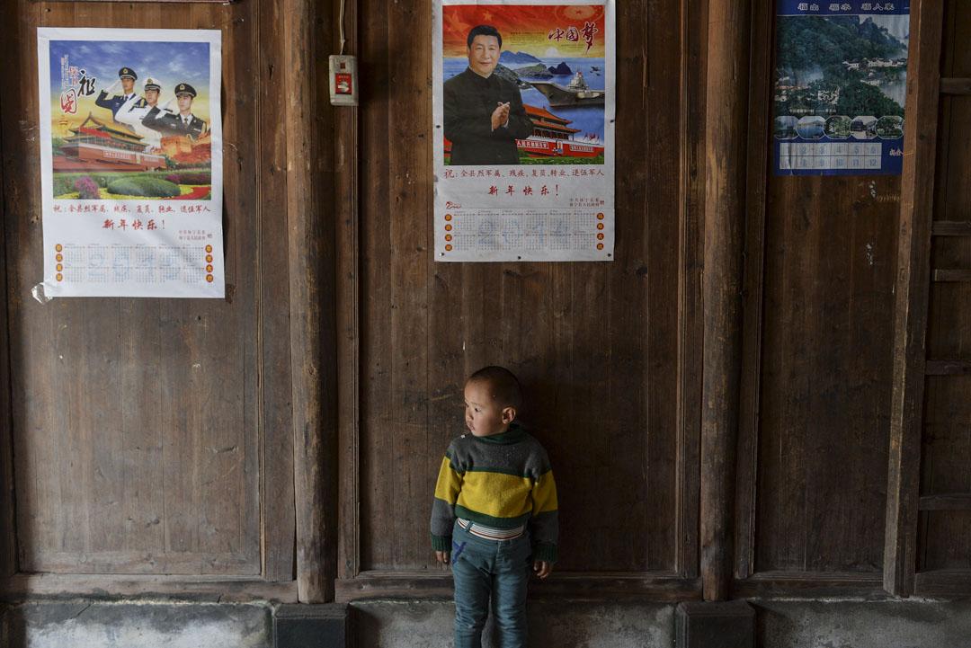 2018年,一名留守兒童站在在國家主席習近平的年曆之下。
