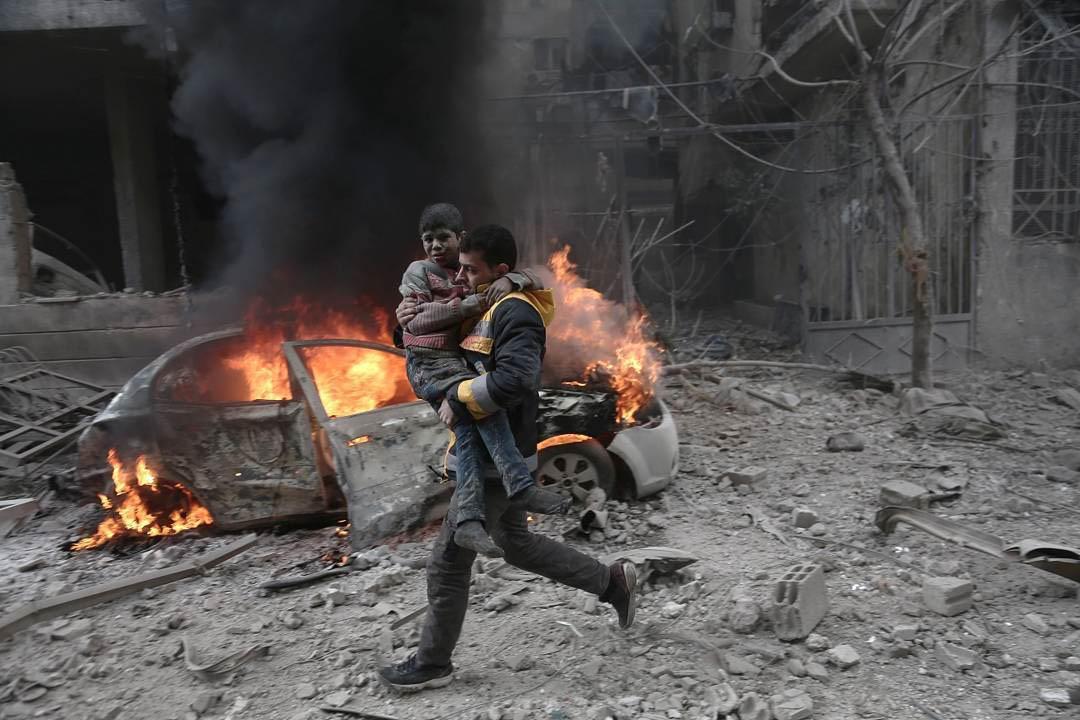 2018年1月6日,敘利亞聯同俄羅斯轟炸被叛軍佔據的東烏塔城鎮 Hamouria,一名救護員抱著一名受傷的男孩離開現場。⠀