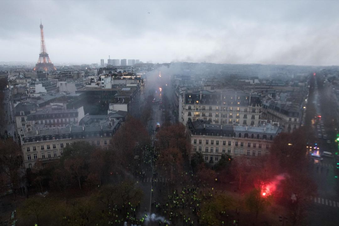 由凱旋門頂處俯瞰煙霧彌漫的巴黎,穿起黃背心的示威者佔據主要道路,與警方對峙。