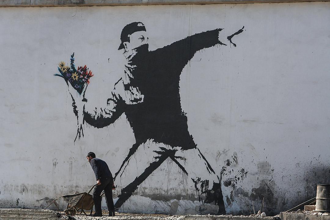 英國當代街頭藝術家班克斯(Banksy),擅長透過在城市空間中以不同塗鴉,帶來視覺衝擊和政治挑戰。  攝:David Silverman/Getty Images