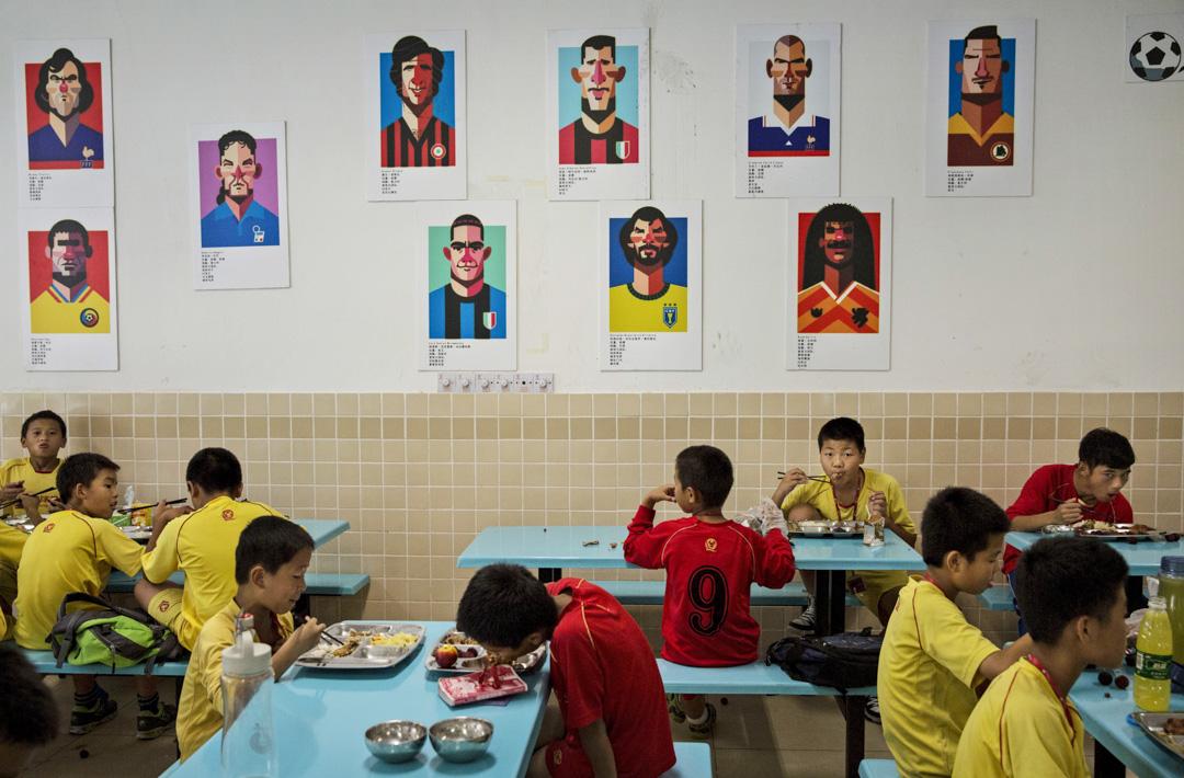 恆大足球學校食堂的牆壁上貼滿了著名足球明星的卡通肖像,受訓的少年足球員在肖像下用膳。 攝:Kevin Frayer/Getty Images