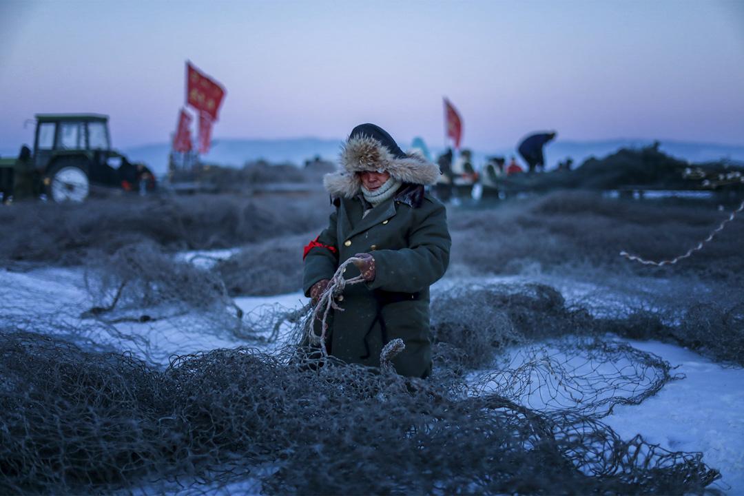 漁民仔細檢查漁網的連接處,確保冬捕的成功。 攝:田衞濤/Imagine China