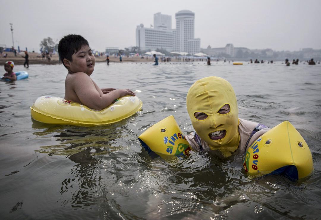 一名中國女子在青島的海灘上戴著頭套游泳。  攝:Kevin Frayer/Getty Images