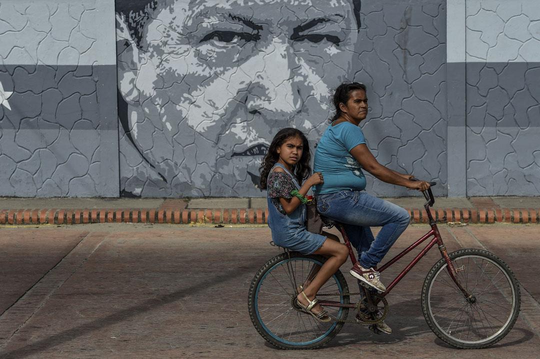 一名婦女和女孩騎着單車穿過已故委內瑞拉總統查韋斯的壁畫。