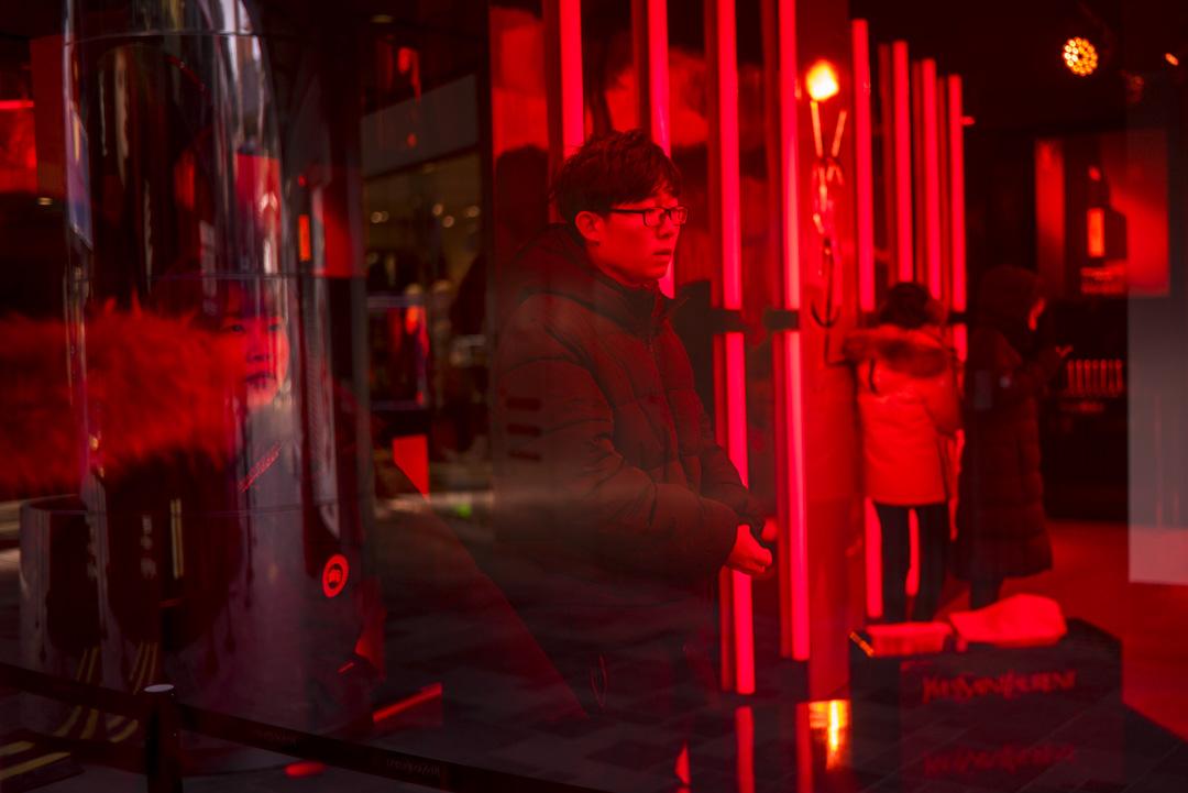 北京一個購物商場,顧客在一個以紅色玻璃為裝飾的展賣空間內參觀。