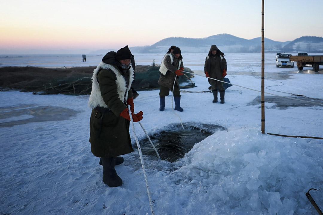 漁民在冰上鑽開一個洞,將漁網放入水中。