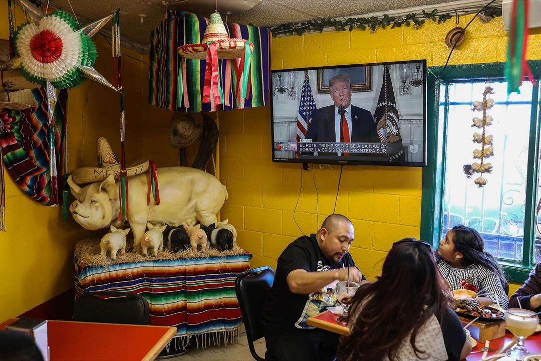 美國德州,Carlos Luna與女兒Dareyna Luna及其家庭在埃爾帕索市的一家墨西哥餐廳裏進餐,電視上播放著美國總統特朗普發表講話的片段。