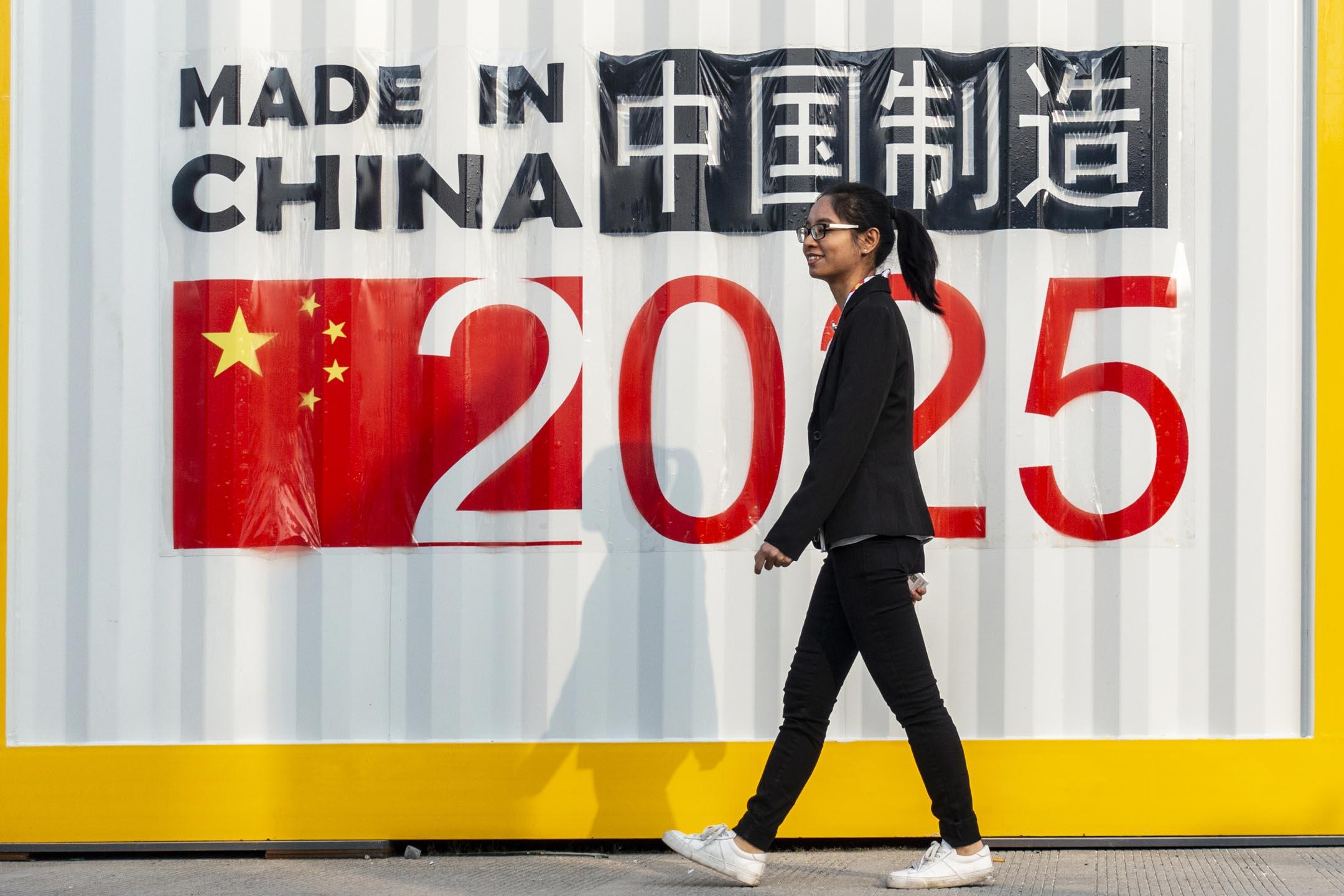 2018年11月29日,上海一個國際機械設備博覽會上,參觀者在印有「中國製造2025」字樣的設備生產企業前路過。 攝:Imagine China