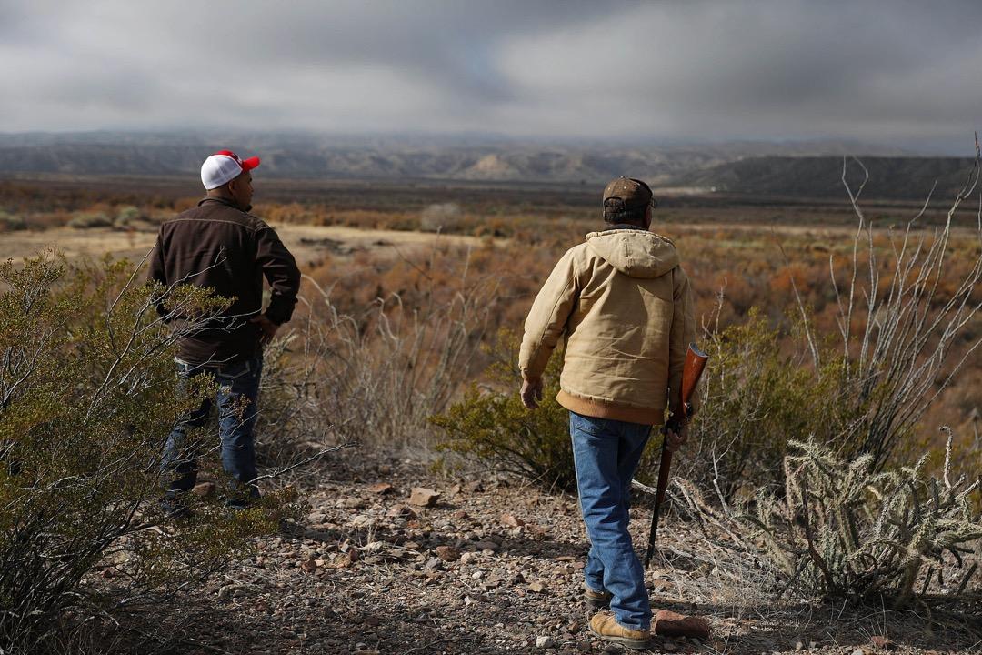 美國德州,Adan Madrid 父子在他們位於坎德拉里亞市的馬場遠觀美墨邊境。