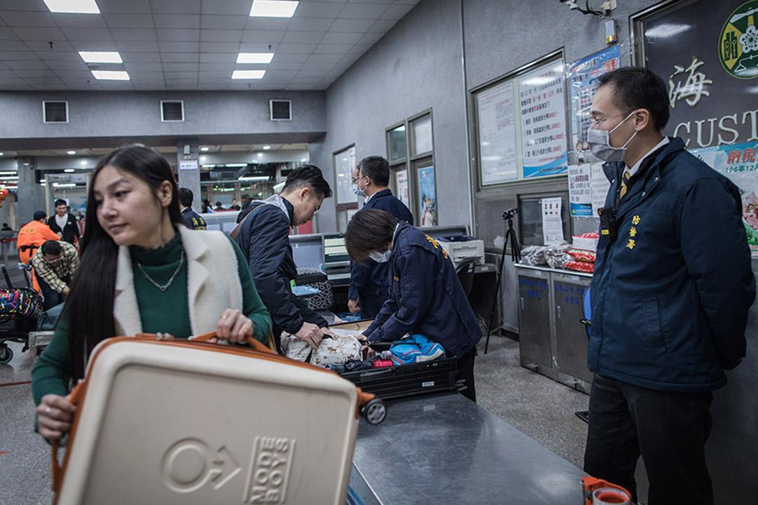 2019年1月4日,金門水頭碼頭工作人員正檢查訪台旅客的行李。