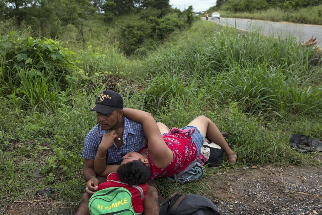 一對同性戀情侶在路邊等待前往薩尤拉的順風車。