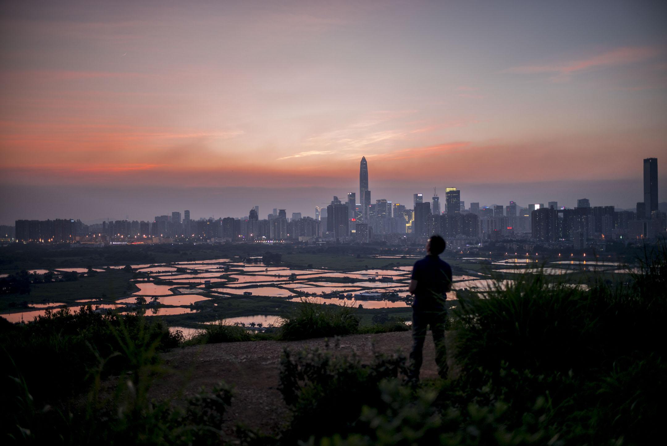 究竟有哪些香港青年落入中國政府的監視網,哪些情況下會被拒入境甚至扣留拷問?外界無從得知。圖為一名青年站在香港的山上,遙看中港邊界。 攝:林振東/端傳媒