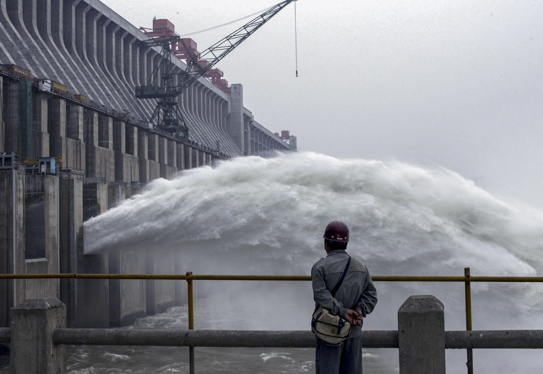 2006年6月6日,湖北省宜昌市,保護其主牆的圍堰在水下爆炸後,一名工人看著三峽大壩開始排放洪水。