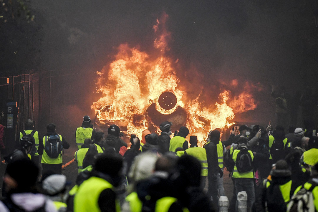 2018年12月1日,法國巴黎發生黃背心運動抗議油價上漲,示威者站在一輛燃燒的汽車前。 攝:Alan Jocard/AFP/Getty Images