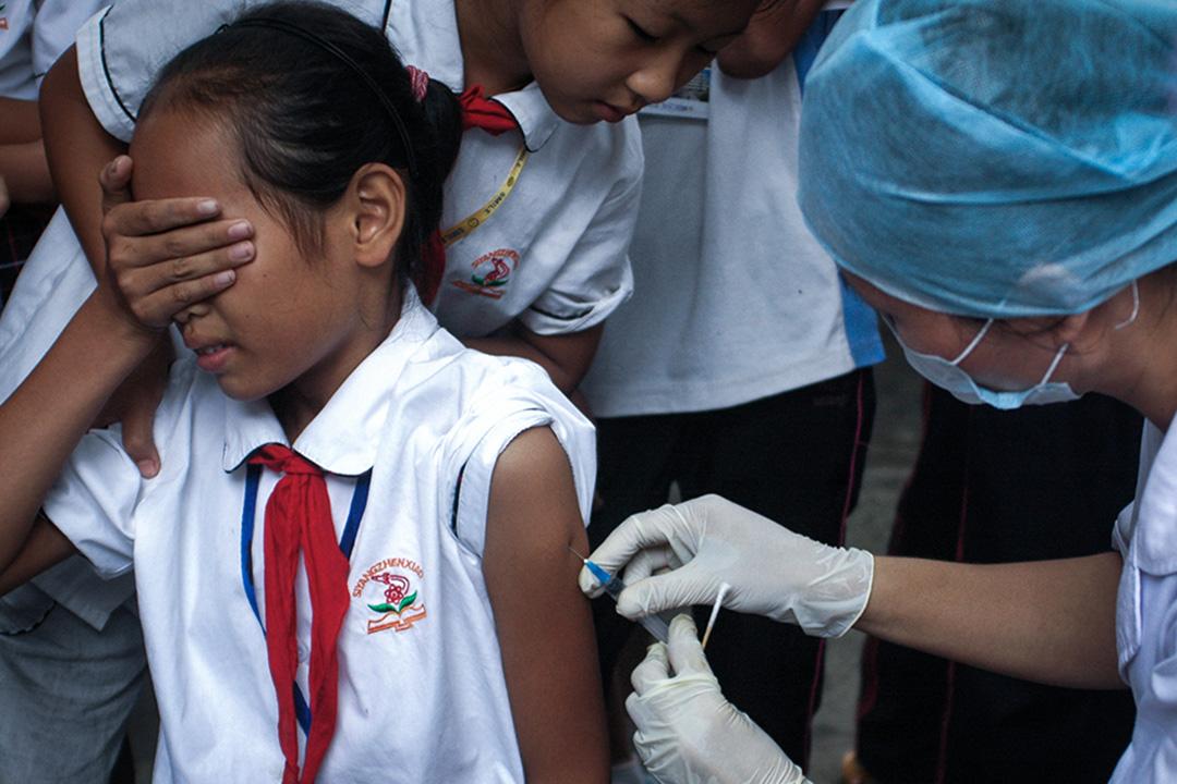 2010年9月13日,在廣西上思縣思陽鎮小學,一位小女生在接種疫苗時,因怕痛捂住了眼睛。