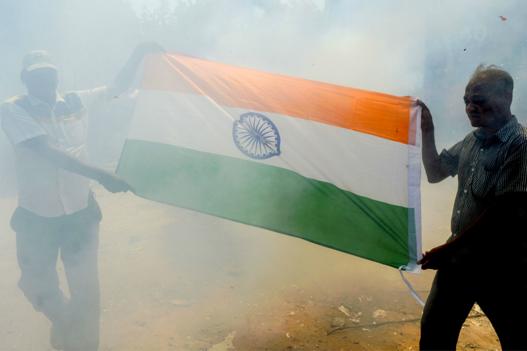 2019年2月26日,印度軍方宣布空襲了克什米爾地區巴基斯坦一側的武裝分子營地,印度居民撐起國旗表達支持。 攝:Arun Sankar/Getty Images