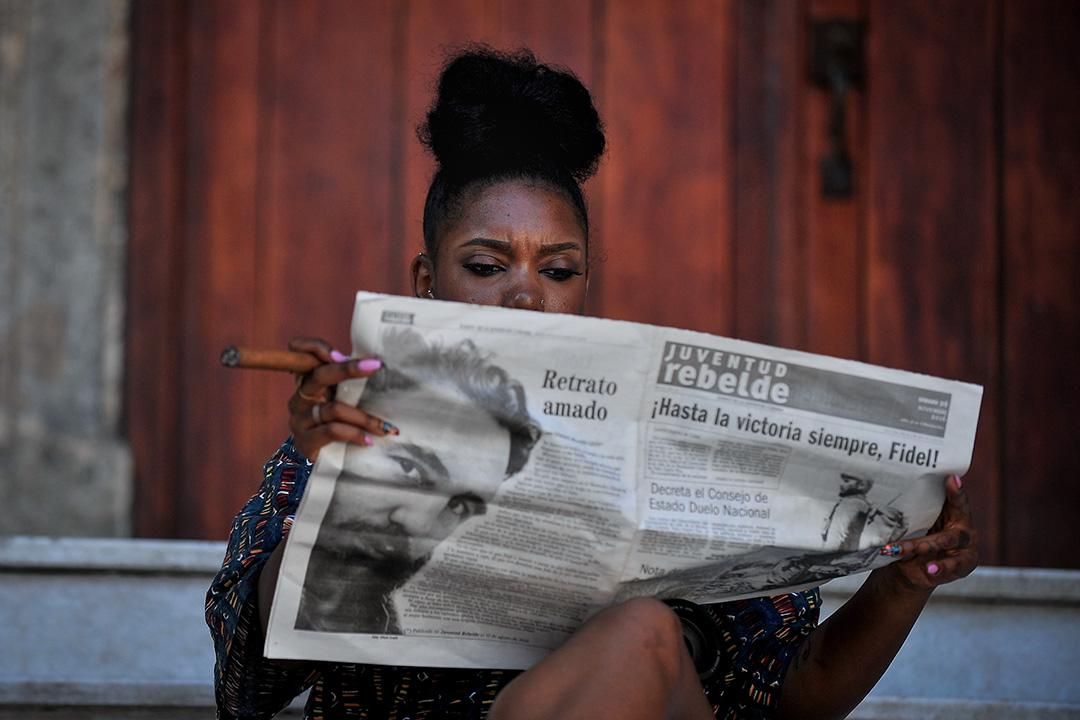 2016年11月26日,古巴革命領袖卡斯特羅去世後的第二天,一名婦女在夏灣拿街頭抽著雪茄讀報。