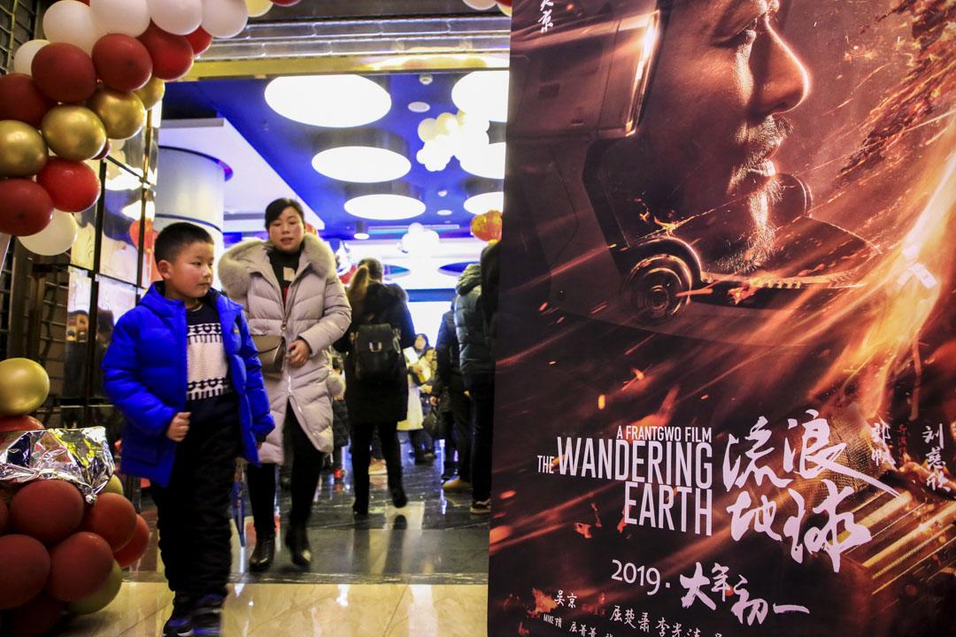 市民從一家電影院的《流浪地球》電影海報旁邊經過。