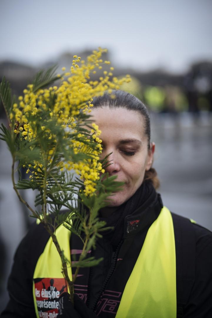 37歲的Audrey是位生產線指揮,她今天帶著含羞草花到巴黎街頭示威,為灰濛濛的巴黎天空增添一點色彩。