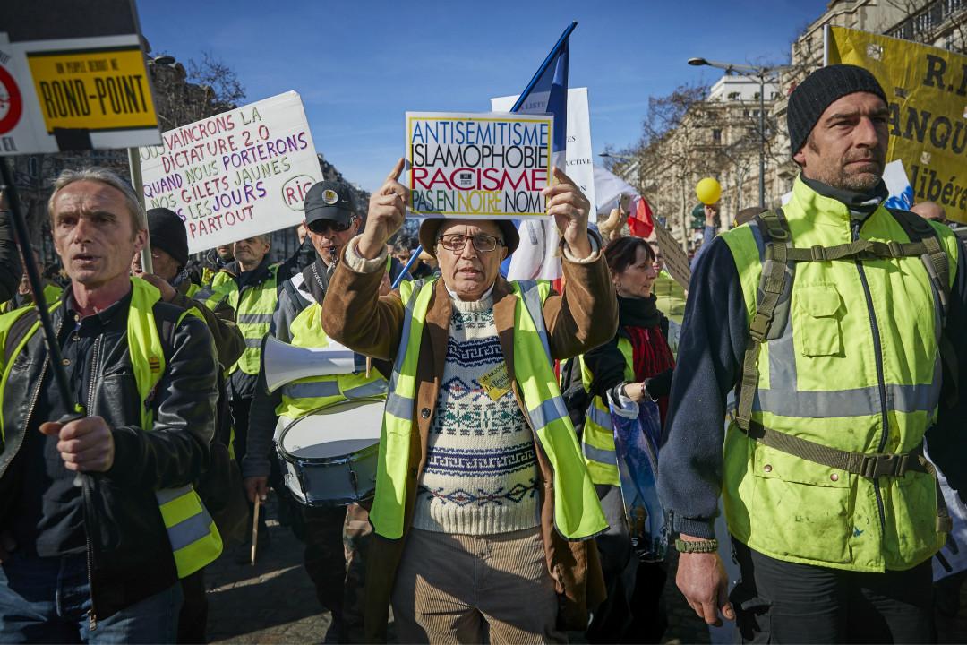 2019年2月17日,法國身穿「黃馬甲」的抗議者走上街頭,手舉標語澄清他們與那些「反猶、反穆斯林的種族主義者」是兩夥人。 攝:Kiran Ridley/Getty Images